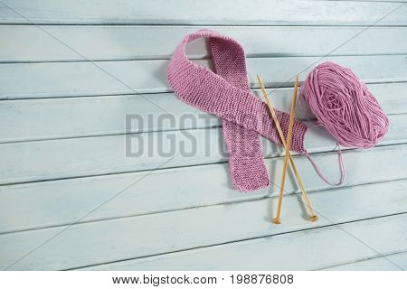 High angle view of pink woolen Breast Cancer Awareness ribbon with crochet needles by yarn on white wooden table