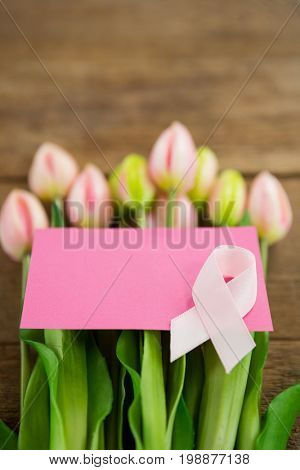 Close-up of pink Breast Cancer Awareness ribbon with blank card on fresh tulips over wooden table