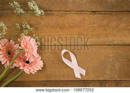 Overhead view of pink Breast Cancer Awareness ribbon by gerbera flowers on wooden table