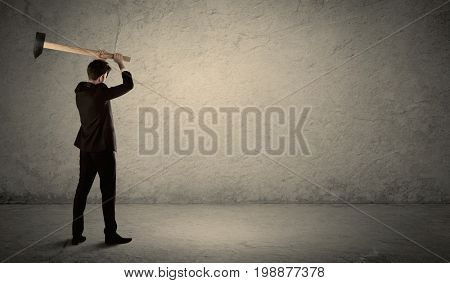 Business man standing in front of a grungy copyspace wall with a hammer