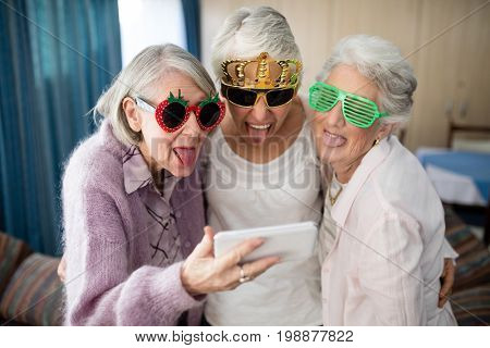 Senior women wearing novelty glasses making face while taking selfie through mobile phone at nursing home