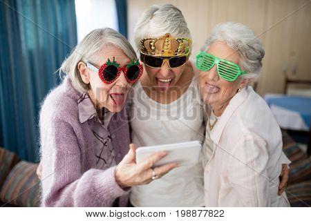 Senior women wearing novelty glasses making face while taking selfie through mobile phone at nursing home