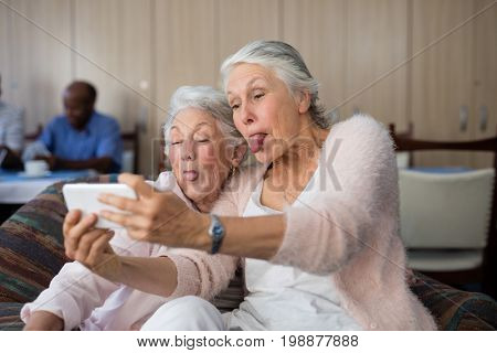 Senior women making face while taking selfie through smart phone at nursing home