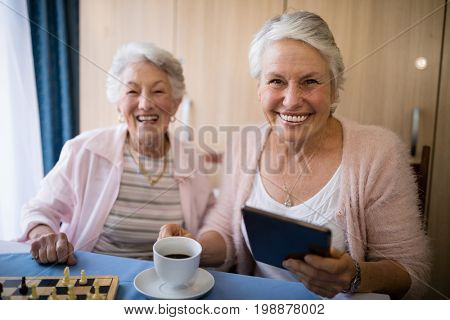 Portrait of smiling senior friends having coffee while playing chess at table in nursing home