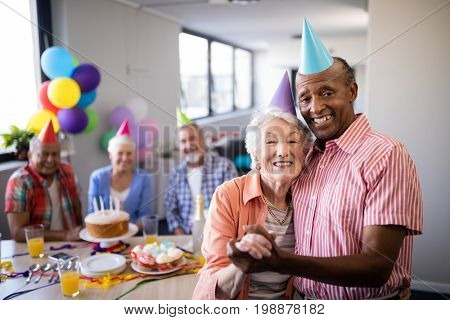 Portrait of senior couple standing by table during birthday party with friends in background