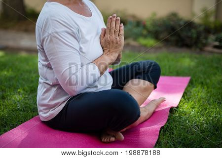 Low section of senior woman meditating in prayer position while sitting on exercise mat at park
