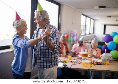 Smiling senior couple dancing by friends enjoying at birthday party