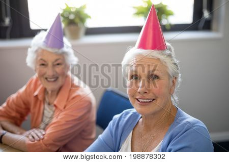 Portrait of smiling senior friends wearing party hats at nursing home