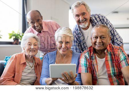 Smiling senior people with digital tablet in nursing home