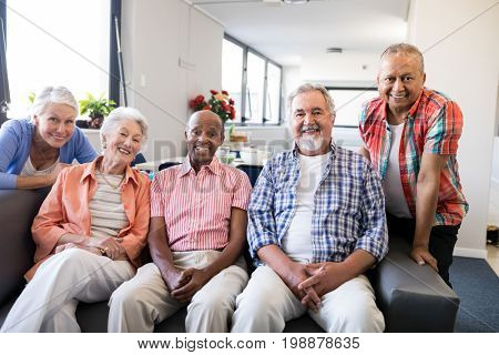 Portrait of multi-ethnic senior people sitting on couch at nursing home