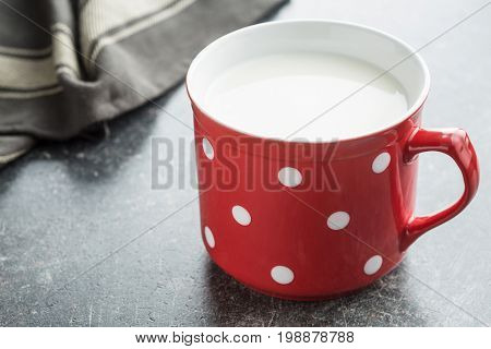 Milk in red mug with white spots. Healthy milk in cup. White cow milk.