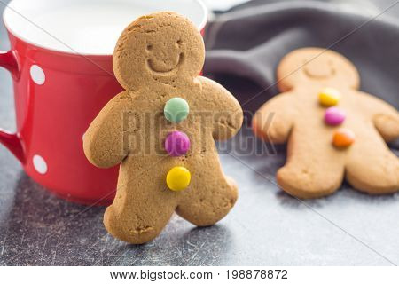 Gingerbread man leaning against a cup on old kitchen table. Xmas gingerbread. Laughing gingerbread man.