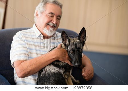 Happy senior man stroking puppy while sitting on armchair at retirement home