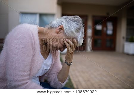 Side view of depressed senior woman sitting on bench with head in hand against nursing home