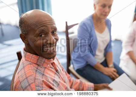 High angle portrait of smiling senior man sitting with females at retirement home
