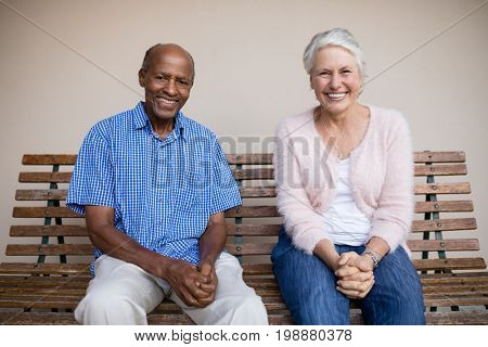 Portrait of smiling senior woman and man sitting on bench against wall at retirement home