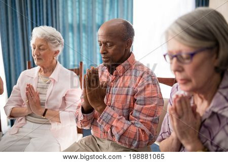 Senior man amidst women praying while sitting on chairs at retirement home