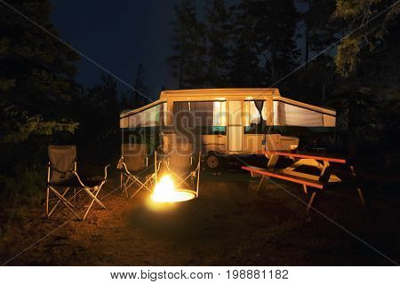 Rv trailer chairs and picnic table around a glowing campfire wilderness site night scene. Outdoors camping adventure and togetherness concepts.