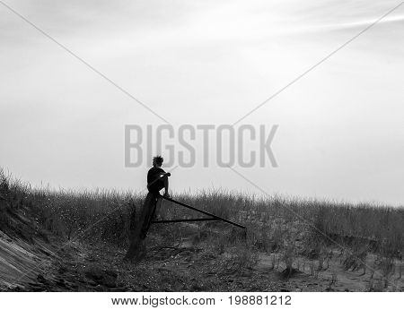 Teenage boy with curly hair sitting on old gate post looking out at field deep in thought silhouette. Black and white background with space for text. Thinking life outdoors and peace concepts.