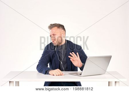 Portrait of middle-aged businessman sitting at office desk and having video call