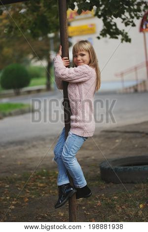photo of young happy girl swinging on the crossbar