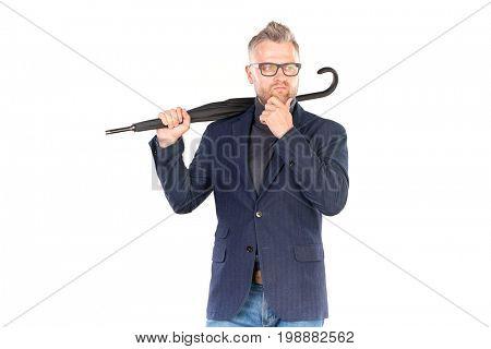 Elegant middle-aged businessman holding closed stick umbrella