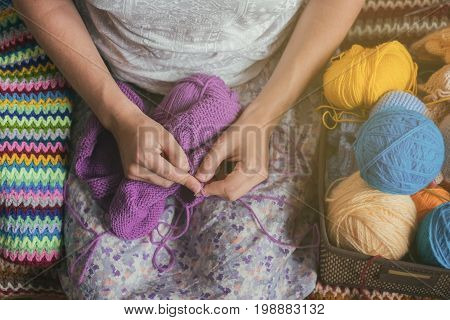 Caucasian woman knits woolen clothes. Holding knitting needles at hands. Prepare for winter