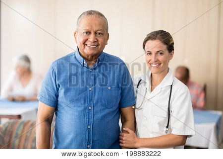Portrait of smiling senior male patient with female doctor standing at retirement home
