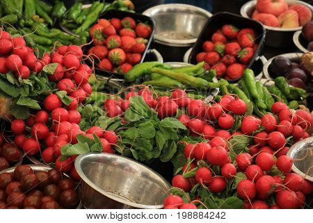 Fresh red radish on a market stall Radish and other vegetables displayed in small metal bowls