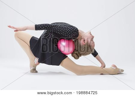 Sport Concepts. Caucasian Female Rhythmic Gymnast In Professional Competitive Black Sparkling Suit Doing Backbend Stretching Exercise With Ball in Studio On White. Horizontal Image