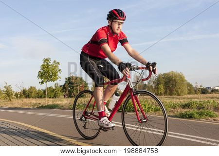 Cycling Concepts and Ideas. Male Caucasian Road Cyclist During Ride on Bike Outdoors. Completely Equipped in Professional Outfit.Horizontal Image Composition