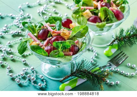 Delicious festive salad with fresh corn salad grapes sausage croutons and nuts Siberian pine in glass vases. Bright color and taste. Colorful salad for Christmas