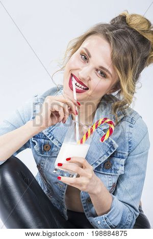 Food and Drinks Ideas. Closeup Portrait of Caucasian Blond Girl Drinking Milkshake Through Straw in Glass. Posing in Latex Pants and Jeans Jacket.Vertical Shot