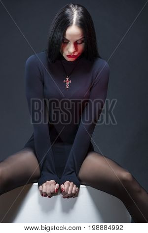 Beauty Concepts. Studio Portrait of Mid Aged Sexy Caucasian Brunette Woman Posing in Black Body Suit with Symbolic Cross Necklace. Vertical Image Composition