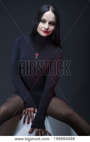 Beauty Concepts. Studio Portrait of Mid Aged Sexy Caucasian Brunette Woman Posing in Black Body Suit with Symbolic Cross Necklace. Vertical Image Orientation