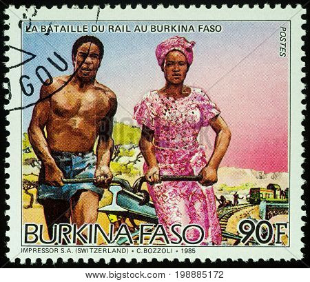 Moscow Russia - August 07 2017: A stamp printed in Burkina Faso shows African man and woman carrying rail series