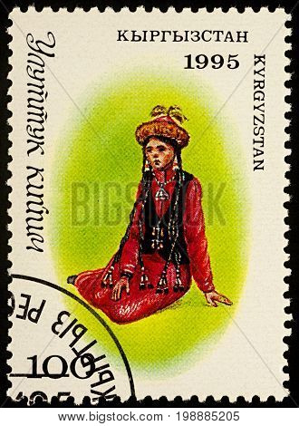 Moscow Russia - August 07 2017: A stamp printed in Kyrgyzstan shows sitting young woman in a traditional Kyrgyz suit series