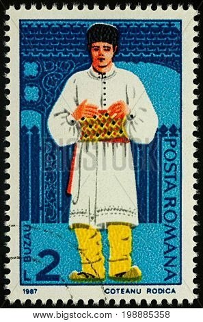 Moscow Russia - August 07 2017: A stamp printed in Romania shows young man in Romanian national costume Buzau region series