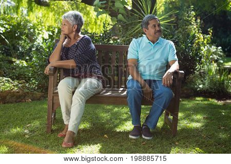 Senior couple arguing while sitting on the bench in the park