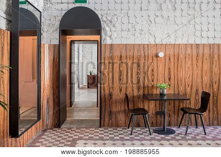 Cafe in a loft style with shabby white walls with textured wooden panel. There is an arch doorway, mirror on the wall, black table with plant in the pot and two chairs, tiled floor with patterns.