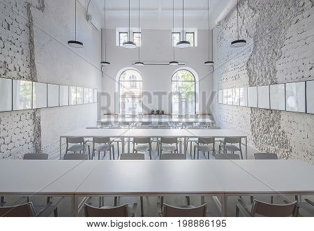 Nice hall in a cafe with shabby light walls and gray floor. There are white tables with chairs, wooden rack with plants in the pots, arch windows, hanging round lamps, frames on the walls. Indoors.