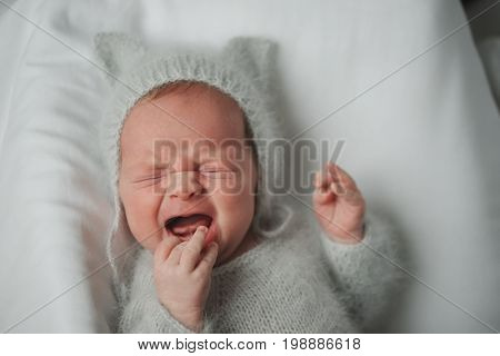 portrait of cute little crying boy at home