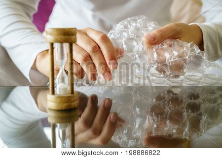 Close-up image of woman's hands popping bubble wrap