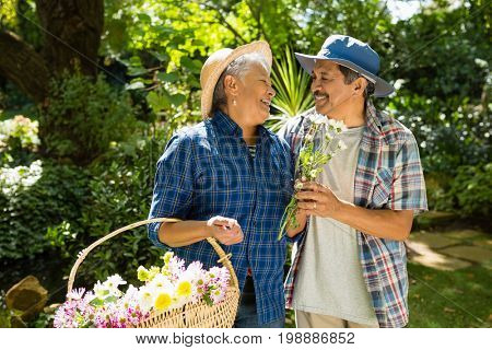 Senior couple walking in garden with flower basket in the park
