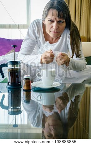 Stressed out mature woman is popping bubble wrap by the coffee table