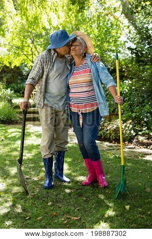 Senior couple kissing each other in garden on a sunny day