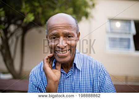 Portrait of smiling senior man sitting against retirement nursing home