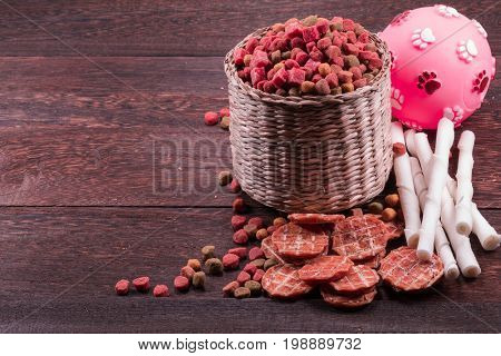 Dog snack, dog chews ,dog biscuits ,ball toy for dog on a grey wooden table wall background with copy space .
