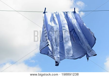 Men's blue shirt dries on the clothesline on clothespins
