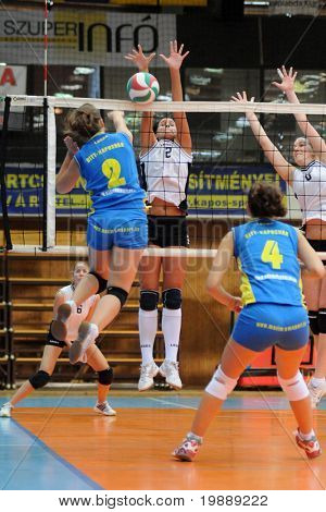 KAPOSVAR, HUNGARY - OCTOBER 10: Zsanett Pinter (L) strikes the ball at the Hungarian NB I. League woman volleyball game Kaposvar vs Veszprem, October 10, 2010 in Kaposvar, Hungary.